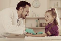 Doctor de sexo masculino que inyecta al pequeño paciente Fotografía de archivo libre de regalías