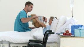 Doctor de sexo masculino que juega con un paciente y su oso de peluche almacen de metraje de vídeo