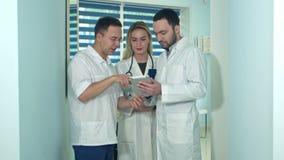 Doctor de sexo masculino que muestra algo en la tableta a sus colegas almacen de metraje de vídeo