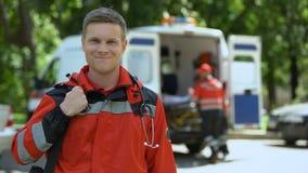 Doctor de sexo masculino que presenta para la cámara, paciente de los transportes del equipo de la ambulancia a la clínica metrajes