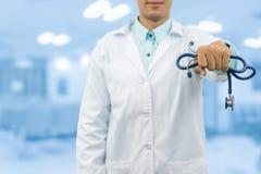 Doctor de sexo masculino que sostiene el estetoscopio en el hospital fotografía de archivo