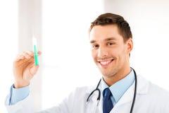 Doctor de sexo masculino que sostiene la jeringuilla con la inyección Imagen de archivo libre de regalías