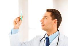 Doctor de sexo masculino que sostiene la jeringuilla con la inyección Fotos de archivo libres de regalías