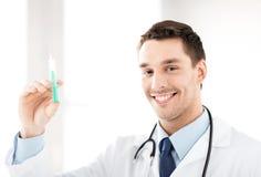 Doctor de sexo masculino que sostiene la jeringuilla con la inyección Fotos de archivo