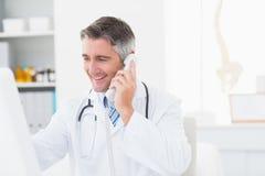 Doctor de sexo masculino que usa el teléfono de la línea horizonte Imagen de archivo