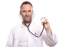 Doctor de sexo masculino sin afeitar sonriente que sostiene un estetoscopio fotos de archivo libres de regalías