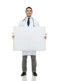 Doctor de sexo masculino sonriente que lleva a cabo al tablero en blanco blanco Imagen de archivo libre de regalías