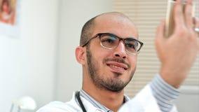 Doctor de sexo masculino sonriente que toma selfies en su teléfono imagenes de archivo