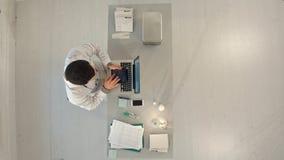 Doctor de sexo masculino de Timelapse que trabaja en una tabla con un ordenador portátil Visión superior imagen de archivo