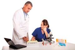 Doctor de sexo masculino y enfermera de sexo femenino que discuten resultados Fotografía de archivo