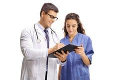 Doctor de sexo masculino y una enfermera con el tablero fotografía de archivo libre de regalías