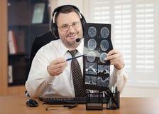 Doctor de Telehealth en las auriculares que revisan imágenes de la exploración de cerebro Imagen de archivo
