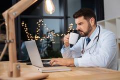 Doctor de trabajo duro serio que tiene un turno de noche imágenes de archivo libres de regalías