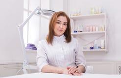 Doctor del cosmetólogo de la mujer en el trabajo en centro del balneario Imagenes de archivo