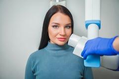 Doctor del dentista que hace a la muchacha paciente de los dientes dentales del tratamiento en oficina dental foto de archivo
