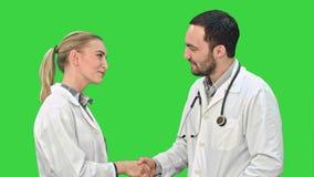 Doctor del hombre joven y enfermera hermosa que sacuden las manos después de la operación acertada y que miran la cámara en una p metrajes
