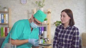 Doctor del hombre que toma una prueba de la saliva de una boca de la mujer joven con un cierre de la esponja de algodón para arri almacen de metraje de vídeo