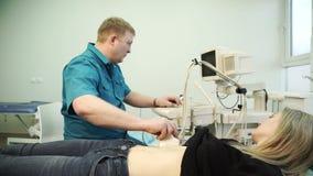 Doctor del pelirrojo que hace el ultrasonido del abdomen de una mujer joven almacen de metraje de vídeo