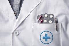Doctor del vestido con las píldoras de las ampollas en bolsillo imagen de archivo