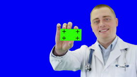 Doctor demonstrates a business card. Chroma key background stock video footage