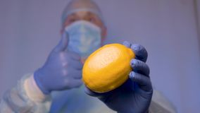 Doctor demonstrates lemon. And shows by gesture that this vitamin is very useful for your health. This is a natural. Remedy for colds. close-up stock footage