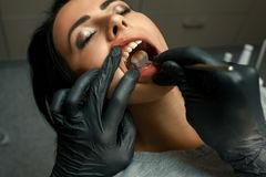 Doctor dentist examines teeth of young woman with mirror. Close stock photos