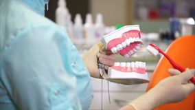 Doctor dentist shows how to properly brush your teeth with a toothbrush