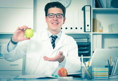 Doctor dentist in uniform demonstrating benefit of apples. Young and smiling doctor dentist in uniform demonstrating benefit of apples Royalty Free Stock Images