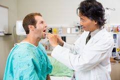 Doctor With Depressor And Otoscope Checking Stock Photo