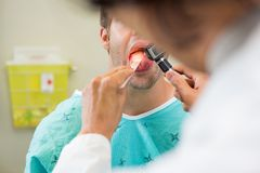 Doctor With Depressor And Otoscope Examining Stock Images