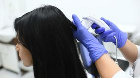 Doctor dermatologist diagnoses the structure of the hair of a young pretty girl with a special tool - a trichoscope. Trichology, trichogram stock footage
