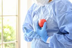 The doctor is describing the heartbeat and heart position on the body. Doctor cardiologist. doctor in surgical clothes holding red stock image
