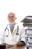 Doctor at desk. Doctor sitting at desk with piles of paperwork Royalty Free Stock Images