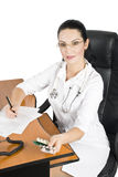 Doctor at desk. Female doctor make a medical prescription with pills,other photos with this model in  Medical Stock Images