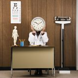 Doctor at desk holding clock over face. Royalty Free Stock Photo