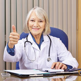 Doctor at desk holding thumbs up Stock Photos