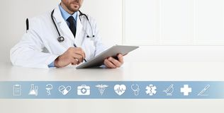 Doctor at desk office write on digital tablet, with symbols and medical icons, web banner and copy space. Template royalty free stock image
