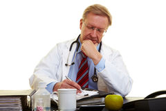 Doctor at desk taking notes Royalty Free Stock Photos