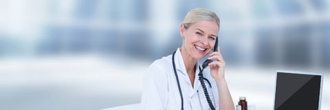 Doctor at desk talking on phone against blurry windows Stock Images