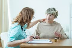 Doctor diagnosing elder woman Royalty Free Stock Image