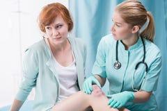 Doctor diagnosing female patient Stock Image