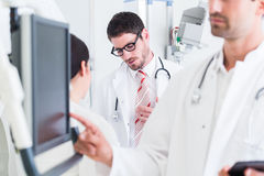 Doctor diagnosing at screen after MRI scan in hospital. Doctors discussing images of x-ray scan in CT Stock Photo