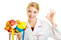 Doctor dietitian recommending healthy food. Diet. Woman in white lab coat holding fruits and colorful measure tapes isolated. Doctor dietitian recommending Stock Images