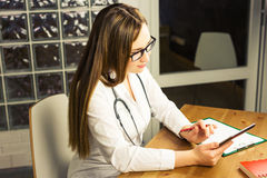 Doctor with digital tablet. Attractive young female doctor in white lab coat working on digital tablet. Royalty Free Stock Photo