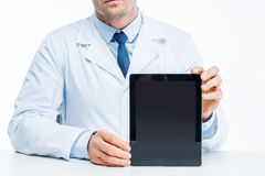 Doctor with digital tablet. Partial view of male doctor holding digital tablet on white Stock Photography