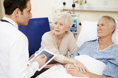 Doctor With Digital Tablet Talking To Couple By Hospital Bed Stock Photo