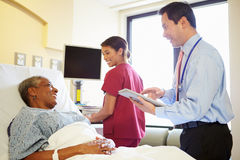 Doctor With Digital Tablet Talks To Woman In Hospital Bed. Looking At Each Other Smiling With Nurse In Background Stock Image