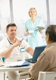 Doctor discussing diagnosis with patient. Smiling doctor discussing diagnosis with patient, smiling nurse holding blood pressure gauge royalty free stock photography
