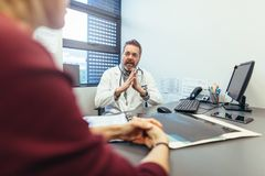 Doctor discussing with female patient in his clinic stock photography
