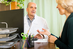Doctor discussing with mature woman Stock Image
